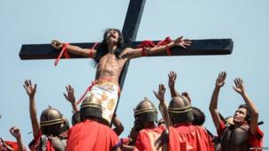 A Catholic devotee tied to a cross is hoisted by participants dressed in soldier wear during a re-enactment of the crucifixion of Christ in Pampanga province, Philippines (18 April 2014)