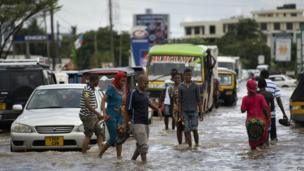 People walking through flood water, Dar es Salaam, Tanzania - Saturday 12 April 2014