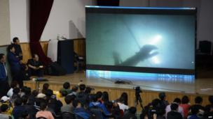 Relatives watch underwater footage of divers searching near the sunken ferry - 19 April