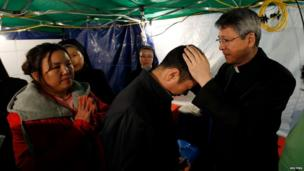 Catholic priest holds a special Easter service for the families of those missing onboard the sunken South Korean ferry Sewol, on 20 April 2014