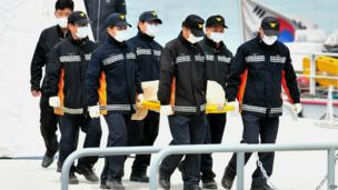 Members of the South Korean rescue team carry the body of a victim recovered from the ferry to an ambulance at the harbour in Jindo - 22 April 2014