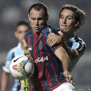 San Lorenzo forward Mauro Matos (front) vies for the ball with Gremio defender Pedro Tonon Geromel