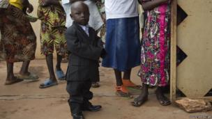 A smartly dressed young boy arrives to attend Easter celebrations at the Saint Joseph Cathedral in Bambari, Central African Republic