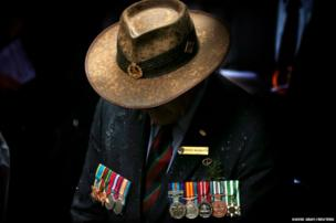 A veteran wearing service medals bows his head during a remembrance service on Anzac Day in central Sydney, Australia