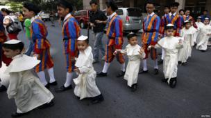 Children wearing Pope's cassocks cross a road before taking part in a parade in Quezon city, Metro Manila April 27