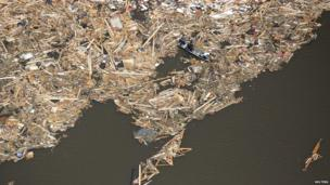 Men use boards as paddles as they search though the debris of what is left of homes in a lake in Vilonia, Arkansas on 28 April 2014.