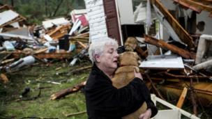 Constance Lambert embraces her dog after finding it alive when returning to her destroyed home in Tupelo, on 28 April