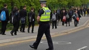 A police officer patrols as pupils arrive for school at Corpus Christi Catholic College in Leeds