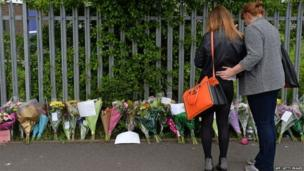 A woman and child look at floral tributes left at Corpus Christi Catholic College in Leeds