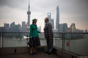 Denmark's Queen Margrethe II and her husband Prince Consort Henrik pose for photographs in front of the Pudong financial district of Shanghai, China