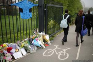 Tributes adorn the school fence as schoolchildren arrive at Corpus Christi Catholic College, in Leeds