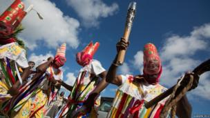 A group of masked dancers, one of whom holds the Queen's Baton.