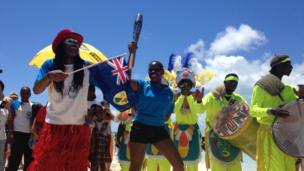 Woman holds Queen's Baton aloft as a carnival band play in the background.