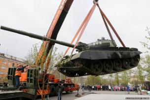 Workers install a demilitarized Soviet-made T-62M1 tank at a memorial in a park in Russia's Siberian city of Krasnoyarsk