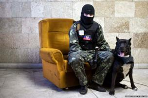A masked pro-Russian protester poses for a picture inside a regional government building in Donetsk, eastern Ukraine