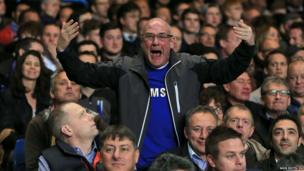 A Chelsea fan tries to encourage his side from the stands