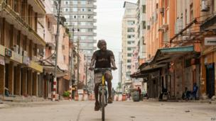 A man cycling in a street in Dar es Salaam, Tanzania - Sunday 27 April 2014