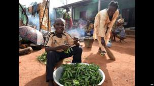 A boy prepares leaves for a meal in a church courtyard in Bouca, CAR - Saturday 26 April 2014