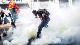 A Turkish protester wearing a gas mask stands amid a fog of tear gas that was fired by riot police to disperse a May Day rally in Taksim Square in Istanbul