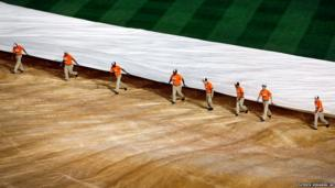 Groundsmen remove a cover from a baseball field