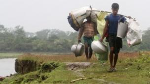 Villagers walk with their belongings after fleeing their violence-affected village of Khagrabari, in the north-eastern Indian state of Assam.
