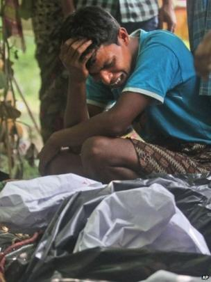 A man cries near the body of a relative, killed in ethnic violence, at a burial ground in the north-eastern Indian state of Assam.