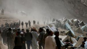 Afghan displaced villagers gather near the site of a landslide at the Argo district in Badakhshan province