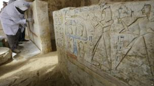 An Egyptian archaeologist cleans a newly-discovered tomb dating back to around 1100BC at Saqqara, a site 30km (19 miles) south of Cairo - 8 May 2014