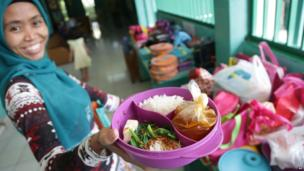 Sri, a house maid, shows a lunch box she prepared for her employer's child, at an elementary school in Jakarta, Indonesia. The lunch consists of rice, meatball soup, and tofu and vegetables.