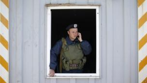 A Ukrainian serviceman speaks on a phone at a checkpoint outside the southeastern port city of Mariupol May 11, 2014