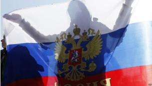 """A woman holds a Russian national flag during a rally to support the self-rule """"referendums"""" for the Ukrainian provinces of Donetsk and Lugansk in central Simferopol on May 11, 2014"""