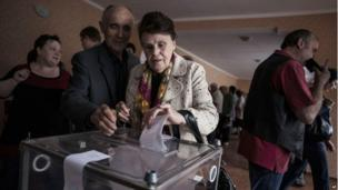 A Ukrainian woman casts her vote at a polling station in the Budennovskiy district, outskirts of Donetsk, Ukraine, Sunday, May 11, 2014.