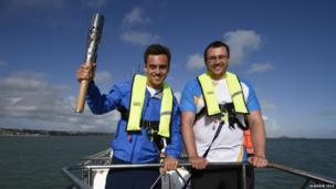 Two men wearing lifejackets pose with the Queen's Baton on board a small boat.