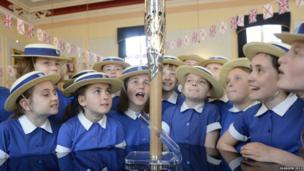 Schoolgirls wearing straw hats look at the Queen's Baton.