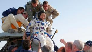 Japanese astronaut Koichi Wakata is helped by ground by search and rescue personnel