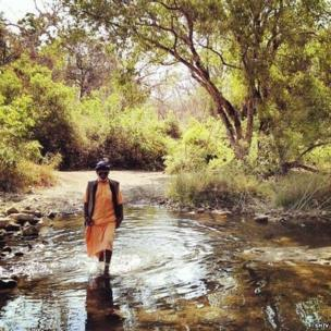 Darshandas – or Bapu, as he prefers to be called, crosses a stream on his way back to his ashram.