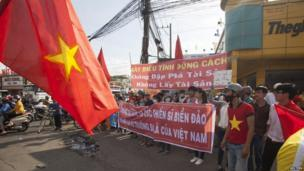 "Workers hold banners, which read, ""Please protest in the right way"" and ""We are looking at soldiers on islands, and the Paracels and the Spratlys belong to Vietnam"", during a protest in an industrial zone in Binh Duong province on 14 May, 2014"