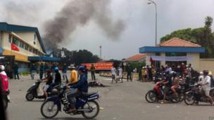 Commuters drive past as riot police stand guard outside a burning factory building in the Vietnamese southern province of Binh Duong on 14 May, 2014