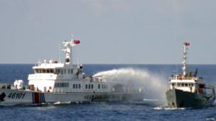 A Chinese coastguard vessel (L) uses water cannon on a Vietnamese Sea Guard ship on the South China Sea near the Paracels islands, in this handout photo taken on 4 May, 2014 and released by Vietnam Marine Guard on 8 May, 2014