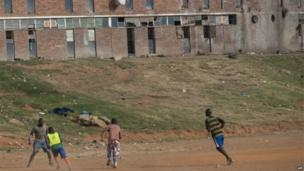 Children play football outside the Madala Hostel on 10 May 2014 in Alexandra township in Johannesburg