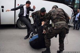 A protester is kicked by Yusuf Yerkel (left), advisor to Turkey's Prime Minister Tayyip Erdogan