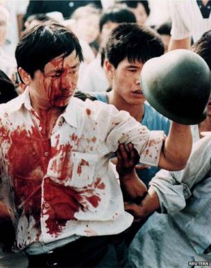 A blood-covered protester holds a soldier's helmet after violent clashes in Tiananmen Square on 4 June 1989