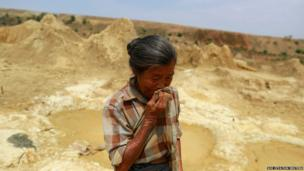 A woman wipes her face as she digs for sulphur sand near a copper mining dum