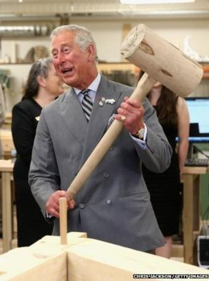 Prince Charles hammers in a peg with a giant mallet