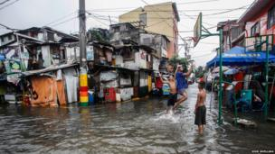 Children play basketball in floodwaters caused by monsoon rains in Makati City, Metro Manila August 19, 2013.