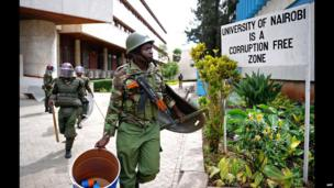 "A police man with tear gas canisters passes by a sign which reads: ""University of Nairobi is a corruption free zone"", Nairobi, Kenya - Tuesday 20 May 2014"