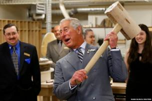 Britain's Prince Charles hefts a wooden mallet at a carpentry exhibit in Charlottetown.