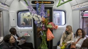 A gardening enthusiast travels on a London Underground District Line train