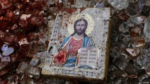 A bloodstained icon of Jesus is seen among blood soaked shattered glass atop a wrecked Kamaz truck near Donetsk airport