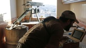 A rebel fighter works on improvised sniper equipment inside a room where he is taking position at the Handarat frontline near Aleppo Central prison in Syria